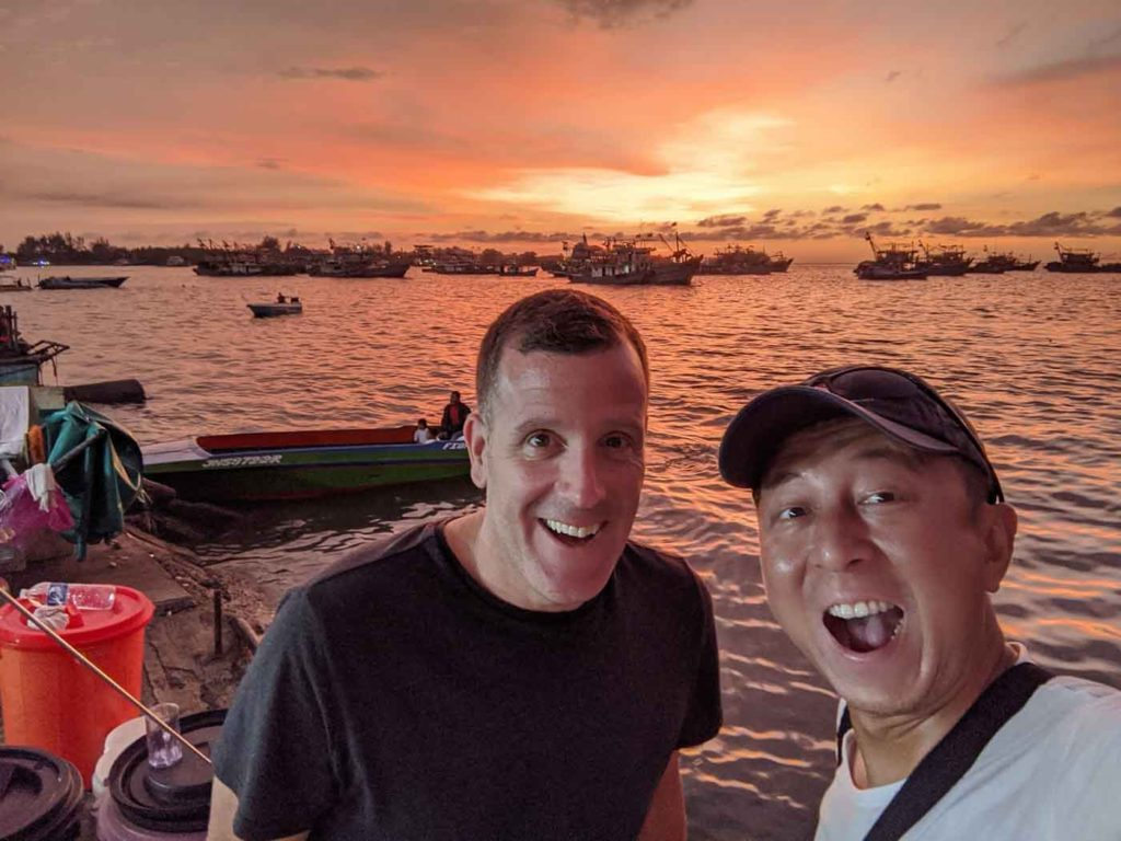 Michael and Halef selfie in front of the waterfront with a fiery orange sunset in the background.
