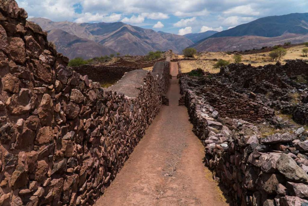 A narrow pathway at Pikillacta. Red, brick colored stones piled several feet high with mud used as mortar.