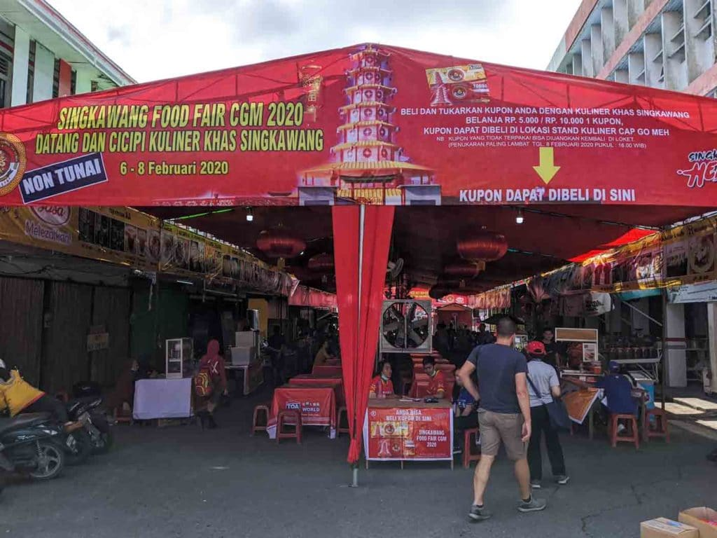 """The entry to the food fair tent for the Singkawan cap go meh festival. The tent reads, """"Singkawang Food Fair CGM 2020"""" in both english and indonesian."""