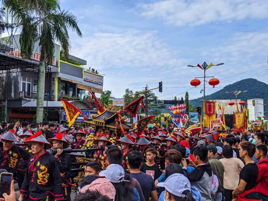 Marchers in black costumes carry a black altar through the streets of Singkawang.