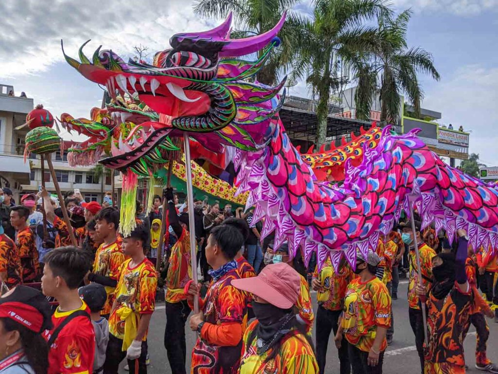 Marchers carry a long, pink and blue dragon through the streets of Singkawang