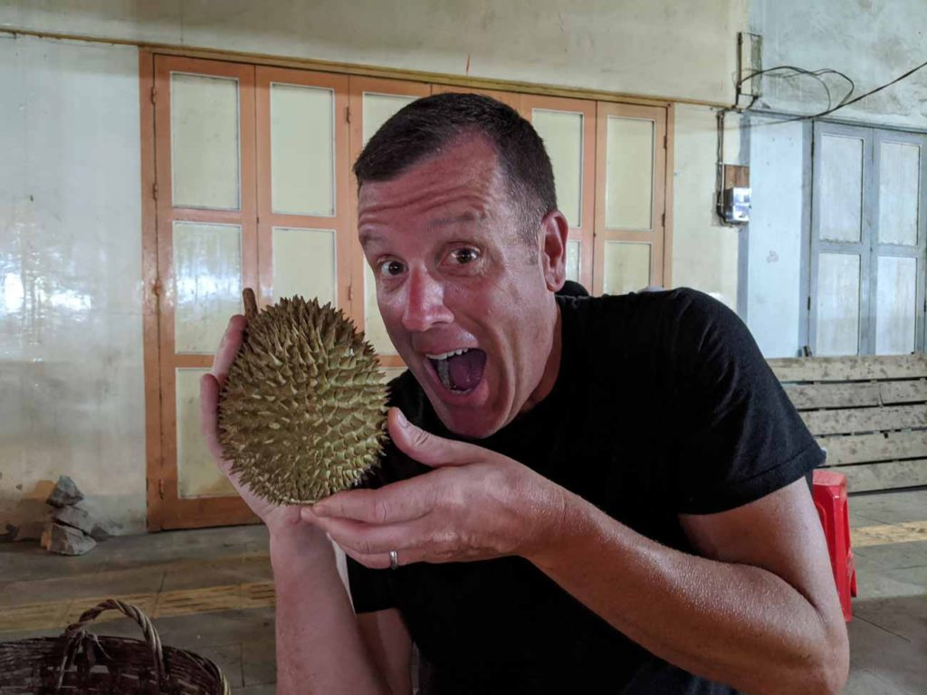 Michael holding a durian fruit we bought in Singkawang