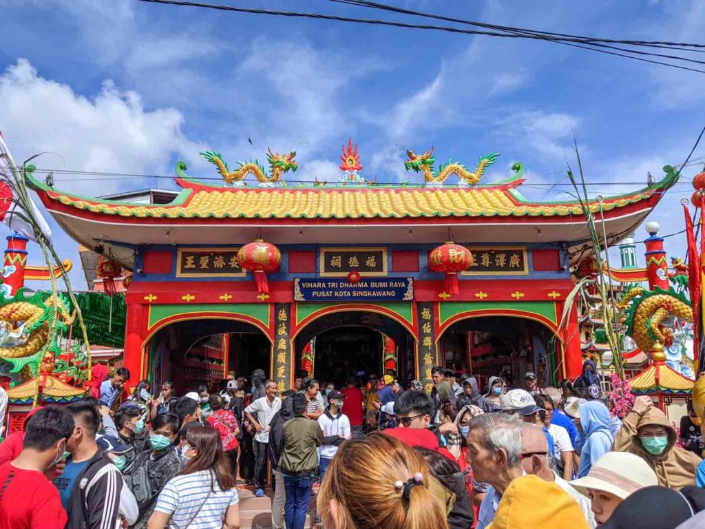 The main temple in the city of Singkawang. A traditional Chinese style roof on a red building. A large crowd is gathered around the temple.