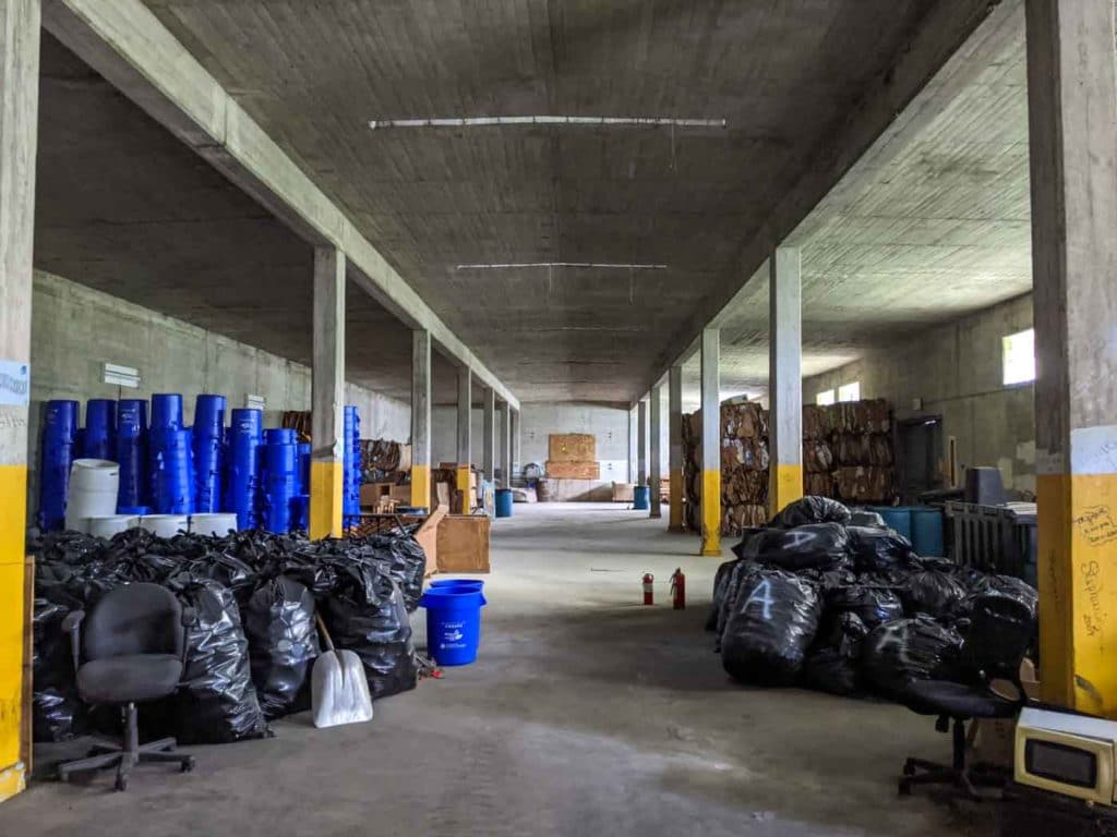 The inside of one of the Vieques bunkers.  On the left and right are large, black plastic construction bags. On the left are stacks of blue recycling bins.