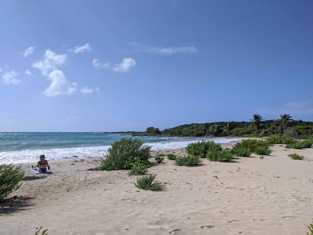A woman laying on a towel on La Chivas Beach in Vieques. The Blue Beach