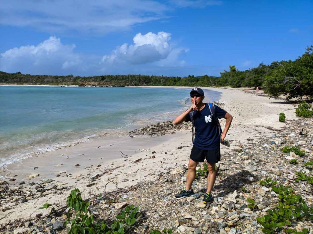 Halef standing on the Secret Beach in Vieques doing a shhhh gesture